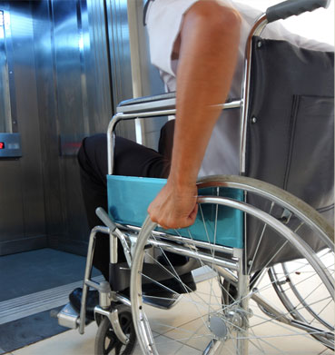 Individual in a wheelchair getting onto an elevator